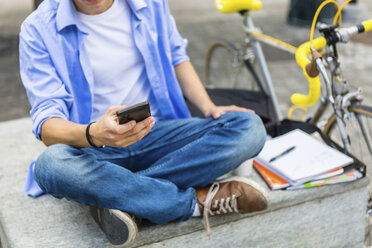 Young man with racing cycle sitting on bench using cell phone - MGIF00143