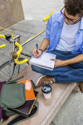 Young man with racing cycle sitting on bench writing on notepad - MGIF00149