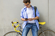 Young man with racing cycle looking at cell phone in front of concrete wall - MGIF00152