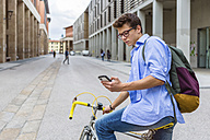 Young man on racing cycle looking at cell phone - MGIF00155