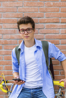 Portrait of young man with racing cycle and cell phone in front of brick wall - MGIF00158