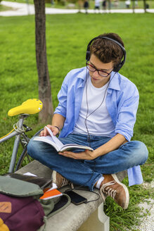 Young man with racing cycle and headphones sitting on a bench reading book - MGIF00167