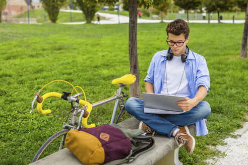 Young man with racing cycle sitting on a bench using laptop - MGIF00170