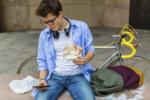 Young man eating pizza on a bench while looking at cell phone - MGIF00176