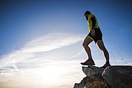 Italy, mountain running man standing on peak - SIPF01795