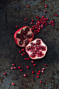 Two halves of pomegranate and pomegranate seed on dark metal - CSF28336
