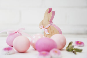 Hand dyed pink Easter eggs with bunny, daisy and catkin decoration on wooden background - GWF05264