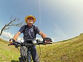 France, Bretagne, Sainte-Anne la Palud, Plage de Treguer, senior man riding mountain e-bike - LAF01915