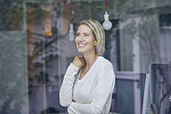 Portrait of laughing blond woman standing behind window pane - PNEF00009