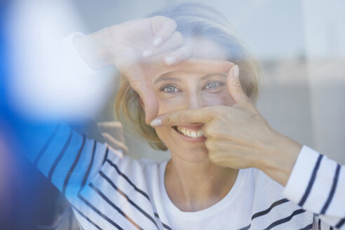 Portrait of laughing blond woman building frame with her fingers while looking at viewer - PNEF00018