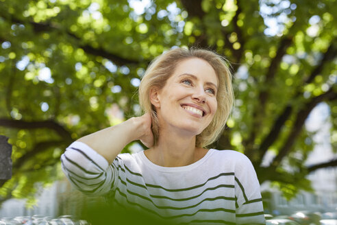 Portrait of happy blond woman in front of a tree - PNEF00021