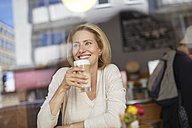 Portrait of smiling woman drinking Latte Macchiato in a coffee shop - PNEF00024