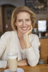 Portrait of relaxed woman with Latte Macchiato in a coffee shop - PNEF00027