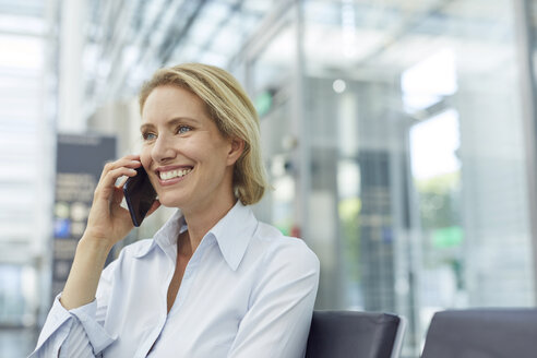 Portrait of laughing businesswoman on the phone waiting at the airport - PNEF00030