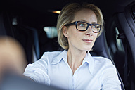 Blond businesswoman wearing glasses driving car - PNEF00039