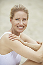 Portrait of laughing blond woman sitting on the beach - PNEF00042