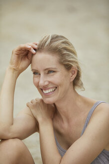 Portrait of laughing blond woman sitting on the beach - PNEF00045