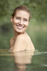 Portrait of laughing blond woman bathing in lake - PNEF00048