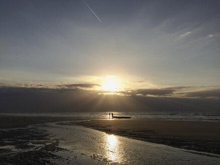 Belgium, Flanders Coast, sundown, people with boat on North Sea beach, low tide - GWF05278