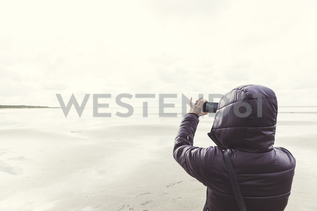 Netherlands, Ouddorp, back view of woman taking selfie on the beach in autumn - CHPF00436