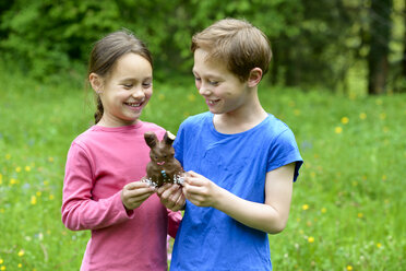 Brother and sister holding chocolate Easter bunny - LBF01667