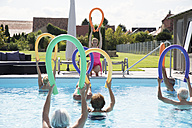 Group of seniors with trainer doing water gymnastics in pool - PNPF00097