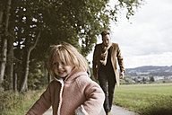 Portrait of blond little girl with  father running after her in the background - KMKF00004