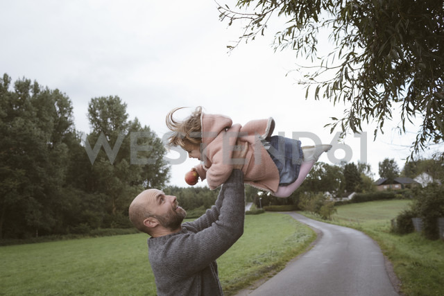 Father holding little daughter aloft - KMKF00010