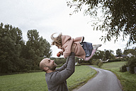 Father holding little daughter aloft - KMKF00010