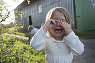 Portrait of screaming little girl covering eyes with her hands - KMKF00016