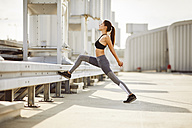 Young woman stretching during city workout - BSZF00046