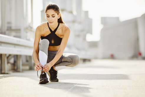 Young woman tying her shoes before workout - BSZF00049