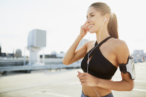 Smiling young woman wearing earphones preparing to work out in the city - BSZF00052