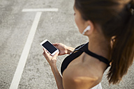 Close-up of woman holding smartphone during workout - BSZF00055