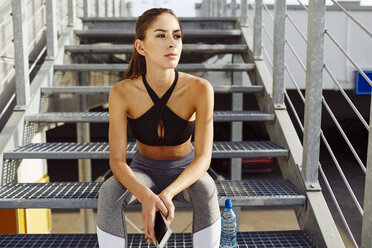 Woman taking break from workout and holding cell phone on stairs - BSZF00058