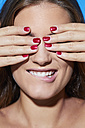 Beautiful young woman with red fingernails covering her eyes - PNEF00060