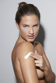 Portrait of beautiful young woman applying skin cream on her arm - PNEF00075