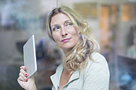 Businesswoman holding tablet behind windowpane - PNEF00087