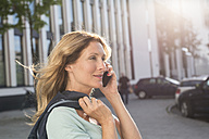 Portrait of woman on cell phone in the city - PNEF00099