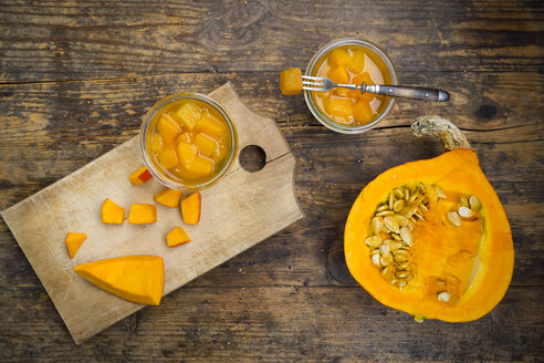 Glass of sweet-and-sour pickled pumpkin and raw pumpkin on wood - LVF06325