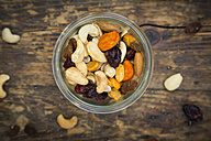 Glass of trail mix on dark wood - LVF06328