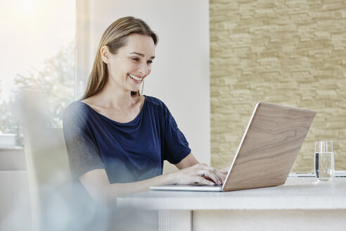 Happy woman at home using laptop - RORF01019