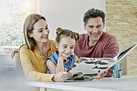 Happy family at home looking at picture book - RORF01022