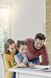 Happy family at home looking at picture book - RORF01025