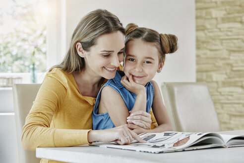 Happy mother with daughter at home looking at picture book - RORF01028