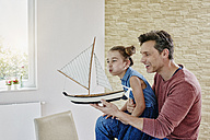 Happy father and daughter playing with model boat at home - RORF01034