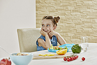 Smiling girl at table packing lunchbox with healthy food - RORF01040