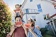 Portrait of happy family with slices of watermelon in front of their home - RORF01046