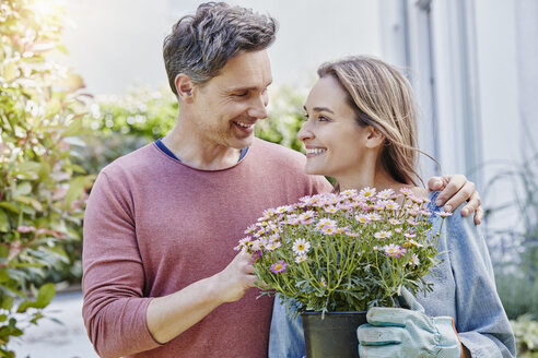 Smiling couple with flowers in front of their home - RORF01049