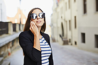 Young woman wearing sunglasses talking on phone outdoors - BSZF00065